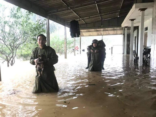 Đồng chí Lê Tuấn Thành cùng đồng đội đang hỗ trợ một cụ già có con đi làm ăn xa đến nơi sơ tán trước khi nước dâng quá cao tại Ngọc Sơn, Hà Tĩnh.