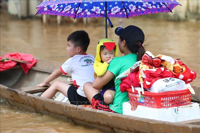 Người dân di chuyển về nhà sau khi nước lũ đã rút. Ảnh: TTXVN