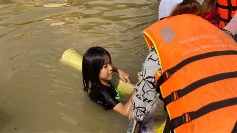 Ôm thân chuối bơi giữa nước lũ để nhận quà cứu trợ