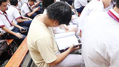 Dự lễ trưởng thành cuối cùng đời học sinh, nam sinh vẫn tranh thủ làm bài tập Hoá dưới sân trường