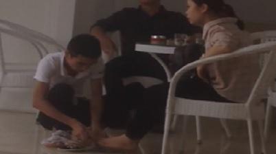 Chàng trai ngồi xuống đất lau dép, lau chân cho bạn gái bị ướt mưa gây nhiều tranh cãi