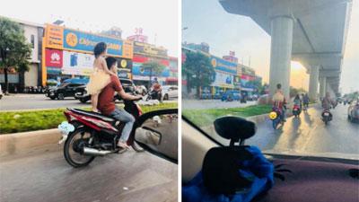 Thót tim cảnh ông bố để con gái nhỏ đứng sau yên xe, không đội mũ bảo hiểm chạy băng băng trên đường