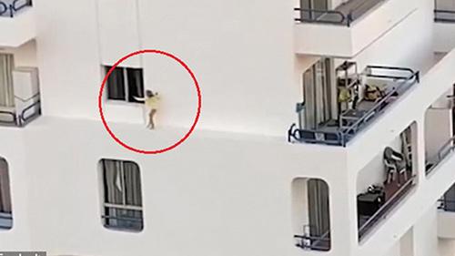 Thót tim bé gái trèo ra cửa sổ, chạy băng băng trên bờ tường hẹp ở tầng 5 toà nhà