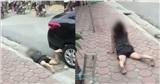 Hết lê la dưới gầm xe ô tô đến bò trên vỉa hè, người phụ nữ khiến đám đông hoảng sợ
