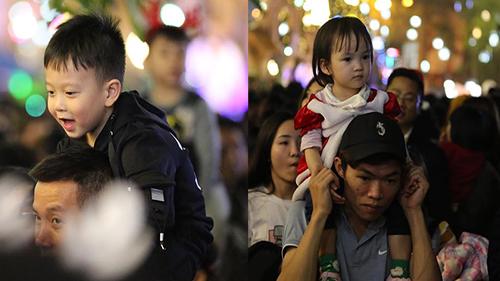 Đêm Giáng sinh đông nghịt người, các em bé được cha mẹ kiệu con lên cổ để tránh bị lạc