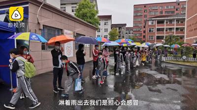 30 giáo viên cầm ô che mưa cho học sinh tiểu học không bị cảm lạnh khi tan học
