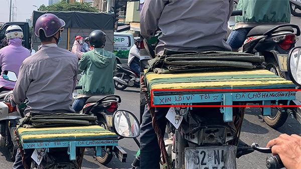 Giữa trưa nắng gắt, người đàn ông lái xe cà tàng gây chú ý với dòng chữ in đỏ gắn ở yên xe