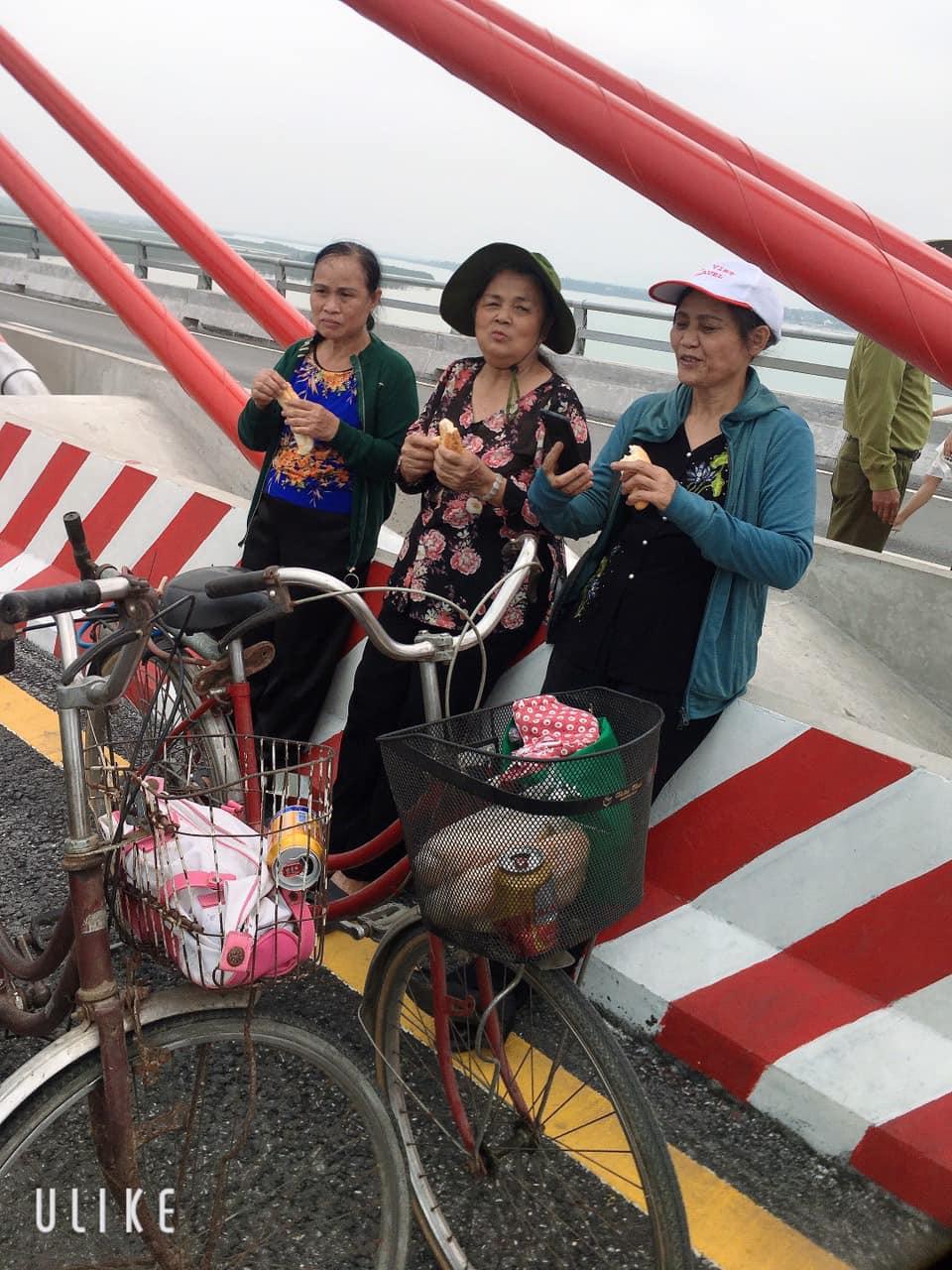 Ba cô dừng chân ăn bánh mì lót dạ trên cầu