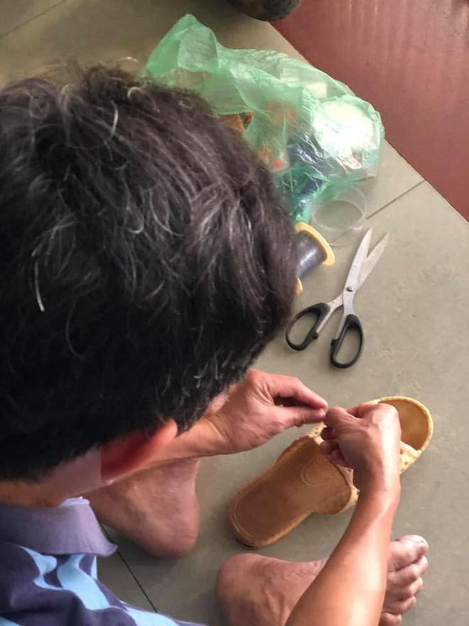 Người đàn ông cặm cụi buộc lại đôi dép tổ ong đã rách sau 2 năm dùng như một thói quen.